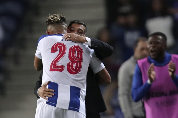 Porto's Soares, left, celebrates with Porto's head coach Sergio Conceicao after scoring the opening goal during the Europa League group G soccer match between FC Porto and Young Boys at the Dragao stadium in Porto, Portugal, Thursday, Sept. 19, 2019. (AP Photo/Luis Vieira)