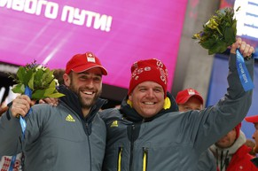 Switzerland's pilot Beat Hefti (R) and Alex Baumann celebrate a second place in the two-man bobsleigh event at the 2014 Sochi Winter Olympics, at the Sanki Sliding Center in Rosa Khutor February 17, 2014.                       REUTERS/Arnd Wiegmann (RUSSIA  - Tags: SPORT BOBSLEIGH OLYMPICS)