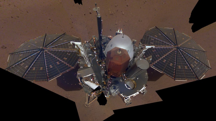 This composite image made available by NASA on Tuesday, Dec. 11, 2018 shows the InSight lander on the surface of Mars. The InSight lander used the camera on its long robotic arm to snap a series of pictures assembled into a selfie. (NASA/JPL-Caltech via AP)