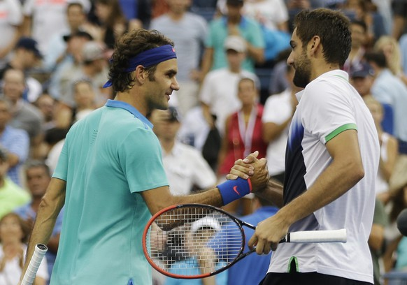 Roger Federer, of Switzerland, left, greets Marin Cilic, of Croatia, after losing to Cilic in their semifinal match of the 2014 U.S. Open tennis tournament, Saturday, Sept. 6, 2014, in New York. (AP Photo/Darron Cummings)