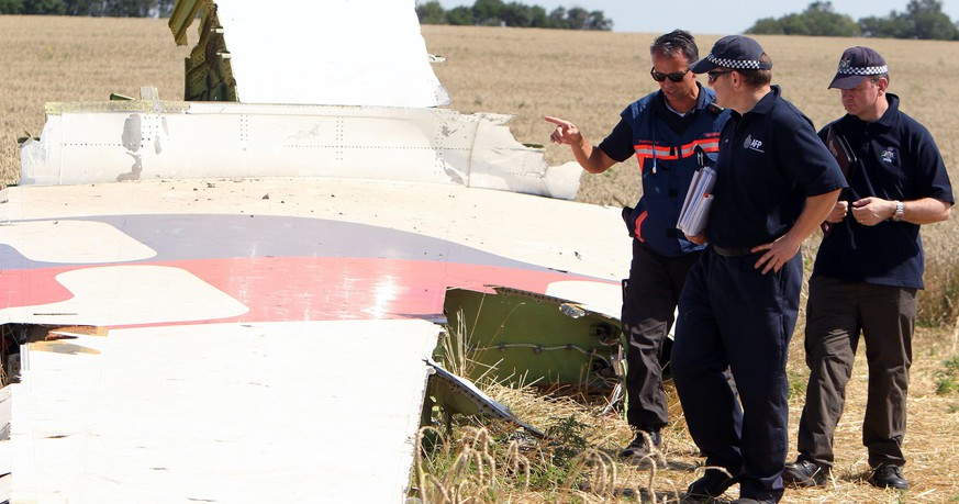 epa04337947 Australian and Dutch investigators examine a piece of debris of Malaysia Airlines Flight MH17 plane, near the village of Hrabove, 100 km from  Donetsk, Ukraine, 01 August 2014. A group of international experts arrived 01 August at the site of the crash of Malaysia Airlines MH17 in eastern Ukraine after the government halted military operations against Russia-backed rebels. The Dutch government said members of the Organization for Security and Co-operation in Europe (OSCE), as well as Australian and Dutch experts, had reached the scene of the crash, where up to 80 bodies could still be laying. Most of the victims on the plane, which is suspected of having been shot down by rebels on July 17, were Dutch, Malaysian and Australian.  EPA/IGOR KOVALENKO