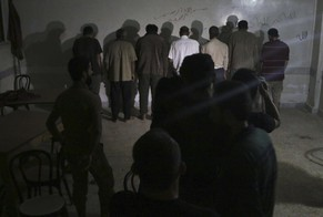 Men suspected of passing on military information to the Syrian government are seen lined up against a wall after being arrested by Free Syrian Army (FSA) fighters, inside an FSA-run prison in Aleppo October 6, 2014. Picture taken October 6, 2014. REUTERS/Abdalrhman Ismail (SYRIA - Tags: POLITICS CIVIL UNREST CONFLICT CRIME LAW)