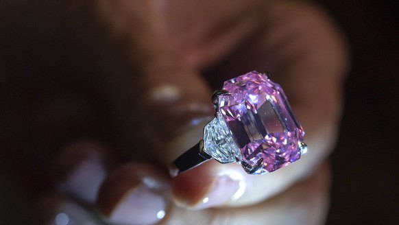 A Christie's employee displays the 18.96 carat fancy vivid pink diamond ''The Pink Legacy'' during a preview at the Christie's, in Geneva, Switzerland, Thursday, November 8, 2018. It is estimated to sell between 30 - 50 millions US dollars. The auction will take place in Geneva, on November 13, 2018. (KEYSTONE/Martial Trezzini)