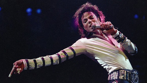 FILE - In this Feb. 24, 1988 file photo, Michael Jackson leans, points and sings, dances and struts during the opening performance of his 13-city U.S. tour, in Kansas City, Mo. Five years after Jackson's untimely death at age 50, the singer remains a pop culture powerhouse, proving to be just as big a moneymaker in death as in life.  He's graced the stage at the Billboard Music Awards via hologram, appears on a new album of unreleased songs and is generating tens of millions of dollars a year - money that will continue to grow and keep Jackson's mother and children living like entertainment royalty.  (AP Photo/Cliff Schiappa, File)