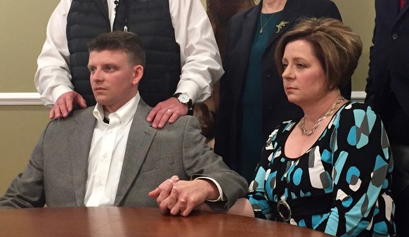 Montgomery Police Officer Aaron Smith, bottom left, holds hands with his mother, Kim Smith, bottom right, during a press conference with attorneys Wednesday, March 2, 2016, in Montgomery, Ala. Smith is charged with murder in the shooting death of Greg Gunn, a black man, outside a neighbor's home, in Montgomery, Ala.  (AP Photo/Kim Chandler)
