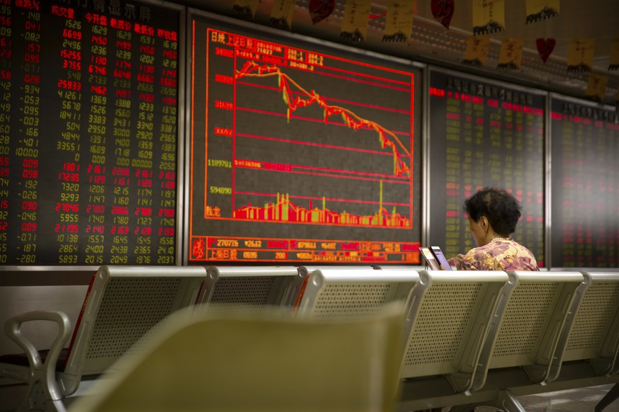 A Chinese investor uses her smartphone as she monitors stock prices at a brokerage house in Beijing, Friday, July 6, 2018. President Donald Trump made clear Thursday that U.S. tariffs against Chinese imports will take effect early Friday and that he's prepared to sharply escalate a trade war between the world's two biggest economies. (AP Photo/Mark Schiefelbein)