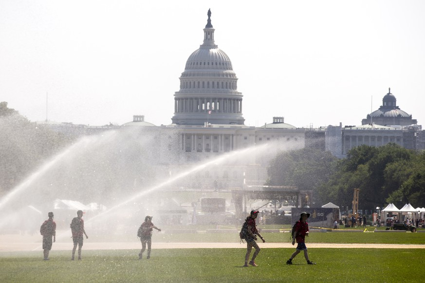 epa07727652 Youths walk under large sprinklers on the National Mall during an excessive heat watch in Washington, DC, USA, 19 July 2019. An excessive heat watch has been issued for the weekend in Washington DC. Meanwhile, a dangerous heat wave will cause close to 200 million people in the US to experience temperatures at 90 degrees Fahrenheit (32.22 Celsius) or higher this weekend, 19-21 July.  EPA/MICHAEL REYNOLDS