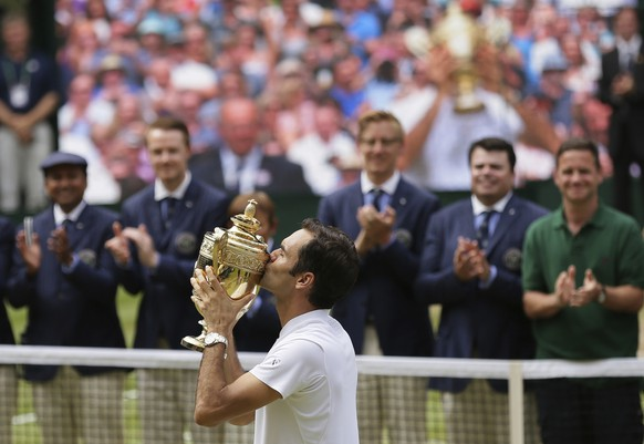 Switzerland's Roger Federer kisses the trophy after defeating Croatia's Marin Cilic to win the Men's Singles final match on day thirteen at the Wimbledon Tennis Championships in London Sunday, July 16, 2017. (AP Photo/Tim Ireland)