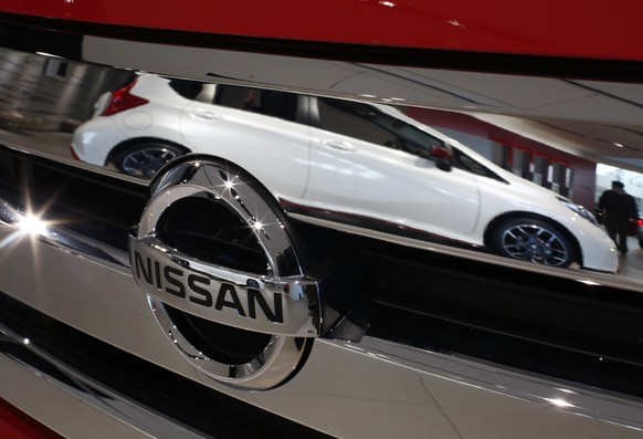 A Nissan car is reflected in a front grill at a Nissan showroom in Yokohama, south of Tokyo, December 18, 2014. Japanese automaker Nissan Motor Co is faring better than peers in Russia as domestic production via an alliance with the country's biggest auto firm shields it against the rouble's plunge, Chief Executive Carlos Ghosn said on Friday. Picture taken December 18, 2014. REUTERS/Thomas Peter (JAPAN - Tags: TRANSPORT BUSINESS LOGO)
