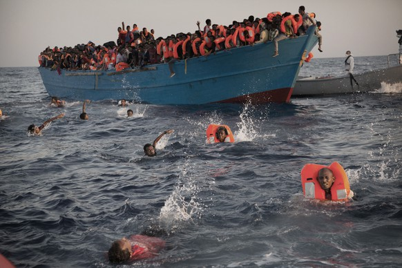 JAHRESRUECKBLICK 2016 - INTERNATIONAL - Migrants, most of them from Eritrea, jump into the water from a crowded wooden boat as they are helped by members of an NGO during a rescue operation at the Mediterranean sea, about 13 miles north of Sabratha, Libya, Monday, Aug. 29, 2016. Thousands of migrants and refugees were rescued Monday morning from more than 20 boats by members of Proactiva Open Arms NGO before transferring them to the Italian cost guards and others NGO vessels operating at the zone. (KEYSTONE/AP Photo/Emilio Morenatti)