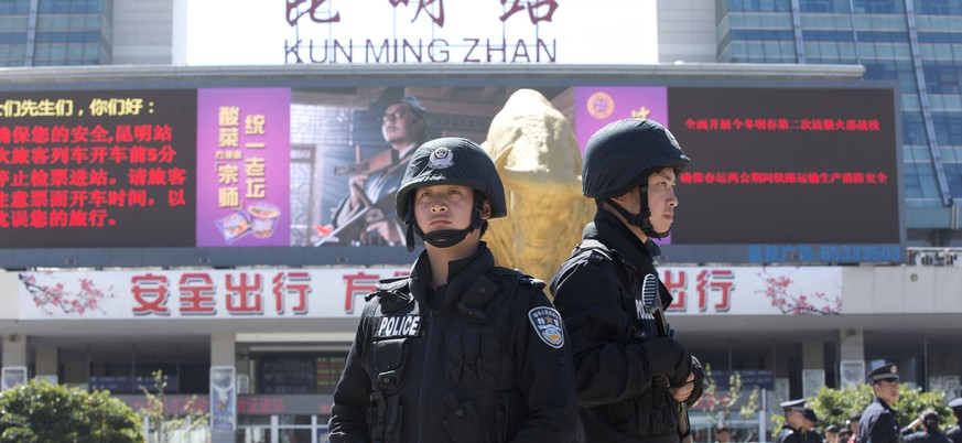 Armed policemen guard their positions in front of Kunming Railway Station in Kunming, in western China's Yunnan province, Sunday, March 2, 2014. More than 10 assailants on Saturday slashed scores of people with knives at the train station, drawing police fire, in what authorities called a terrorist assault by ethnic separatists based in the far west, state media said Sunday. (AP Photo/Alexander F. Yuan)