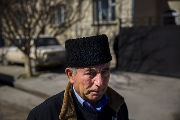 Mustafa Asaba, a regional leader of Crimean Tatars, stands outside a friend's home in Belogorsk near the Crimean capital of Simferopol March 17, 2014. Among the voices drowned out by victory celebrations across Crimea as it voted to leave Ukraine and join Russia were those of the Tatars, a minority group for whom the prospect of a return to Moscow rule brings fear and uncertainty. Picture taken March 17, 2014.  REUTERS/Thomas Peter (UKRAINE - Tags: POLITICS SOCIETY)