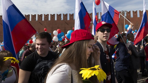 Balloons and national flags fly over crowd as people prepare to walk on Red Square to mark May Day in Moscow, Russia, Monday, May 1, 2017, with the St. Basil's Cathedral in the background. As in Soviet times, people paraded across Red Square, but instead of red flags with the Communist hammer and sickle, they waved the Russian tricolor. (AP Photo/Ivan Sekretarev)