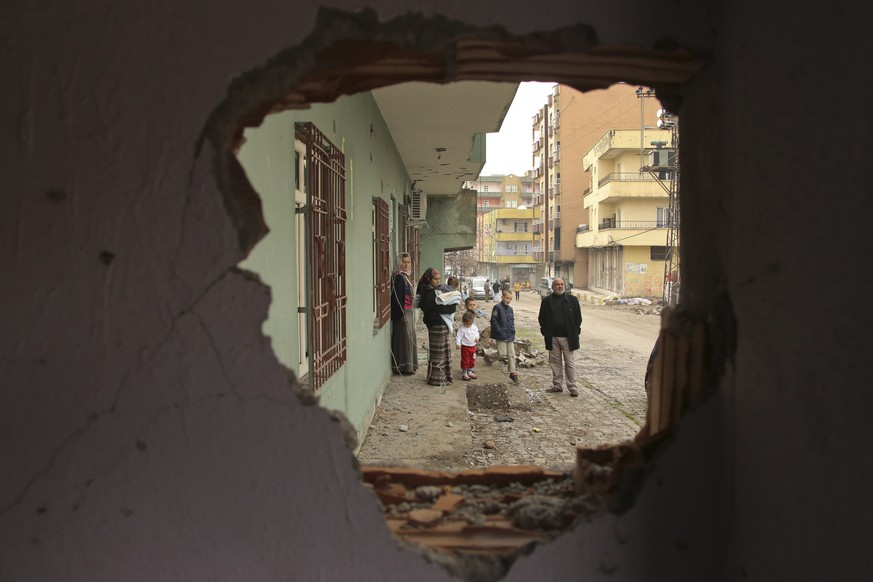 Residents are seen through a hole in a damaged building in the mostly-Kurdish town of Silopi, in southeastern Turkey, near the border with Iraq, Tuesday, Jan. 19, 2016. Turkey's prime minister announced Tuesday that military operations against Kurdish rebels have ended in one mainly Kurdish southeastern town. The military is still fighting militants linked to the Kurdistan Workers' Party, or PKK, in two other urban areas. (AP Photo/Mahmut Bozarslan)