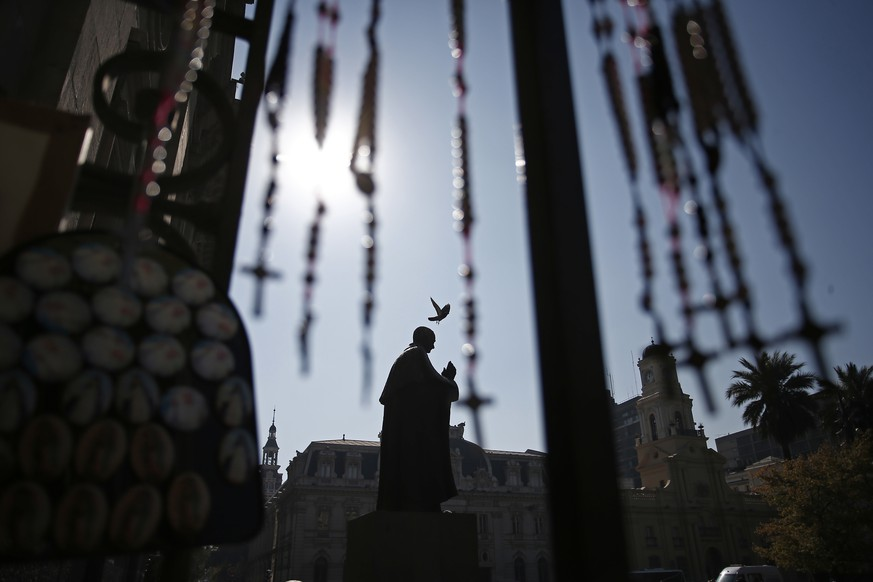 A pigeon flies over the statue of Cardinal Jose Maria Caro, in front of the Santiago Cathedral, in Santiago, Chile, Friday, May 18, 2018. In the biggest shake-up yet in the Catholic Church's long-running sex abuse scandal, every active Chilean bishop offered to resign Friday over what Francis said was their