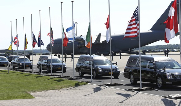 The convoy of hearses with the remains of the victims of Malaysia Airlines MH17 downed over rebel-held territory in eastern Ukraine, drives past international flags as it leaves Eindhoven airport to a military base in Hilversum July 23, 2014. Two aircraft carrying the remains of some of the 298 passengers who died on flight MH17 touched down at an airport in the Dutch city of Eindhoven on Wednesday, as next-of-kin and Dutch and foreign officials looked on. The remains of the victims of the downing of the flight over eastern Ukraine, 193 of whom were Dutch, will be brought over the next few days to a military base in Hilversum, the Netherlands. The Netherlands declared Wednesday the country's first day of mourning in more than half a century.          REUTERS/Francois Lenoir (NETHERLANDS  - Tags: TRANSPORT POLITICS DISASTER CIVIL UNREST)