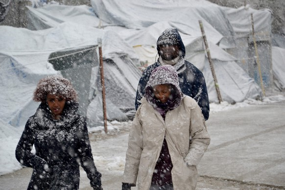 epa05708050 Refugees walk in the snow at the Moria refugees camp on Lesvos Island, Greece, 09 January 2017. A cold wave across Greece causing temperatures to drop drastically brought snowfall to many cities.  EPA/STRATIS BALASKAS