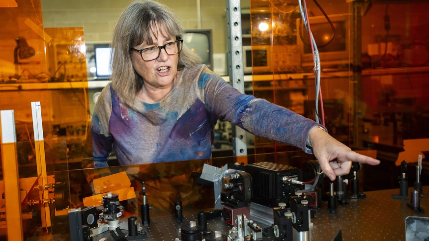 epa07064774 Canadian Donna Strickland, an associate physics professor at the University of Waterloo, demonstrates her laser apparatus after being awarded the 2018 Nobel Prize for Physics, in Waterloo, Canada, 02 October 2018. Strickland was awarded the prize alongside American and French scientists for their work in laser physics.  EPA/WARREN TODA