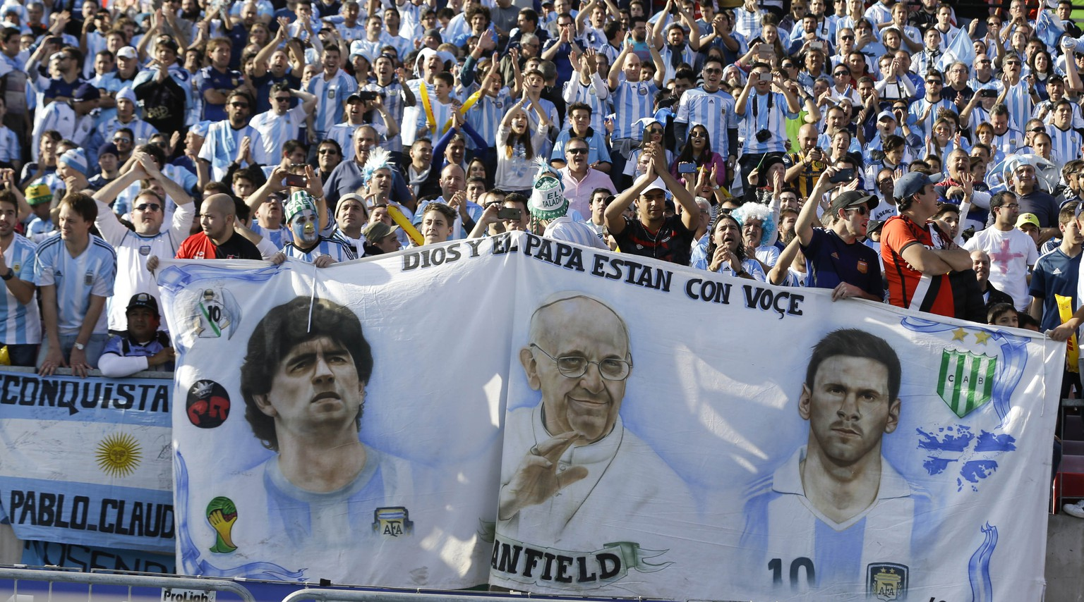Argentina's fans hold a banner with the images of Argentina's Lionel Messi, right, Pope Francis, center, and Argentina's soccer legend Diego Maradona, during the final Copa America soccer match between Argentina and Chile at the National Stadium in Santiago, Chile, Saturday, July 4, 2015. (AP Photo/Ricardo Mazalan)