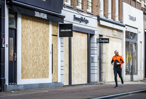 epa08977286 Retailers in the PC Hooftstraat have barricaded their business in Amsterdam, Netherlands, 31 January 2021. The entrepreneurs in the chic shopping street fear damage if riots break out.  EPA/Remko de Waal