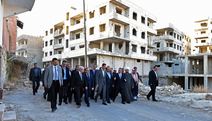 In this photo released by the Syrian official news agency SANA, Syrian President Bashar Assad, center, walks on a street with officials after performing the morning Eid al-Adha prayers in Daraya, a blockaded Damascus suburb, Syria, Monday, Sept. 12, 2016. Syrian President Bashar Assad says his government is determined to