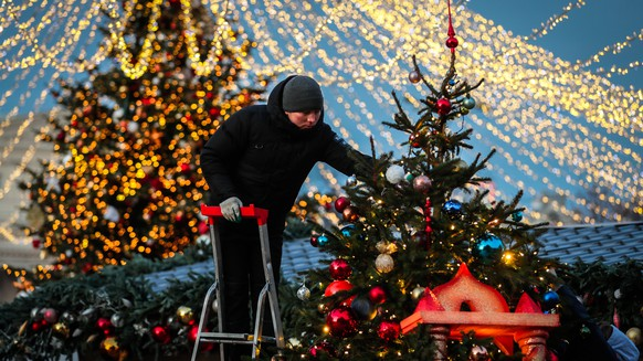 epa08083727 A man installs decoration on Christmas trees near Red Square decorated for the New Year and Christmas holidays in the center of Moscow, Russia, 20 December 2019.  EPA/YURI KOCHETKOV