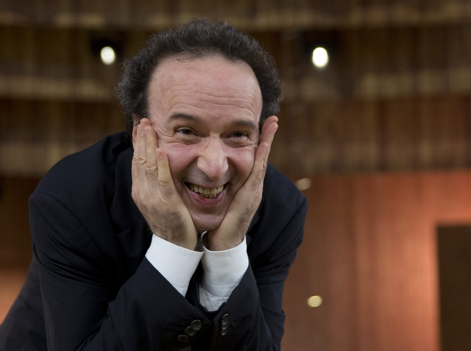 Italian actor Roberto Benigni smiles as he poses for photographers before the rehearsal of his show