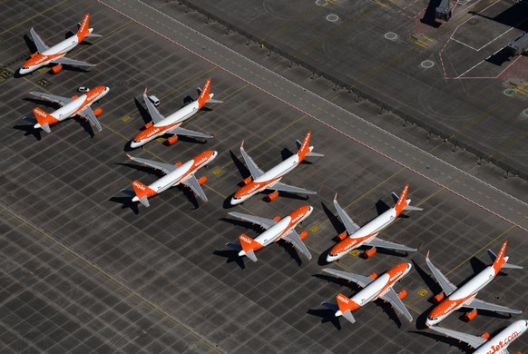 epa08519899 (FILE) - An aerial view shows air planes of EasyJet sitting on the tarmac at the Berlin Brandenburg International Airport BER  in Schoenefeld, Germany, 23 April 2020 (reissued 01 July 2020). German labour union Ver.di on 01 July 2020 said EasyJet, a British low-cost airline with its headquarters in London, that currently has 34 aircraft stationed in Berlin, plans to halve the number of planes in Berlin to 18 by the end of 2020. Ver.di also claimed the company plans to halve the number of employees in Berlin from 1,540 to 738. Berlin is Easyjet's only German base with planes and staff.  EPA/OLIVER LANG *** Local Caption *** 56050976