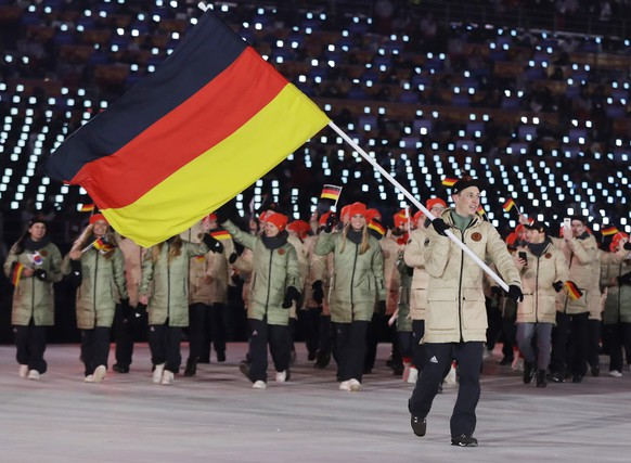 Eric Frenzel carries the flag of Germany during the opening ceremony of the 2018 Winter Olympics in Pyeongchang, South Korea, Friday, Feb. 9, 2018. (AP Photo/Petr David Josek)