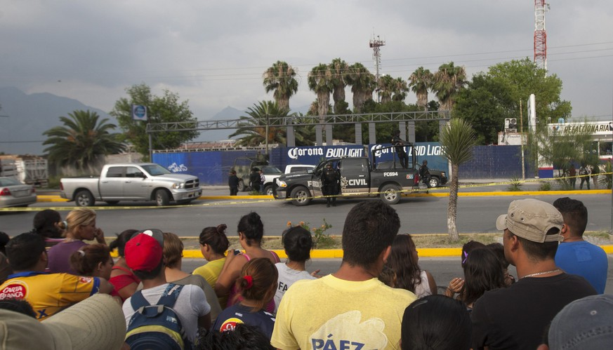 epa04809880 A crowd observes the crime scene where a group of armed men killed ten people in a beer distribution center in the municipality of Garcia, 40 kilometers from Monterrey, Mexico, 19 June 2015.  EPA/STR