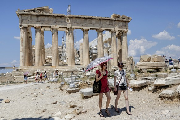 Tourists walk trough the ancient Acropolis hill, with the ruins of the fifth century BC Parthenon temple on the background in Athens, Monday, June 29, 2015. Anxious Greeks lined up at ATMs as they gradually began dispensing cash again on the first day of capital controls imposed in a dramatic twist in Greece's five-year financial saga. Banks will remain shut until next Monday, and a daily limit of 60 euros ($67) has been placed on cash withdrawals from ATMs. (AP Photo/Daniel Ochoa de Olza)