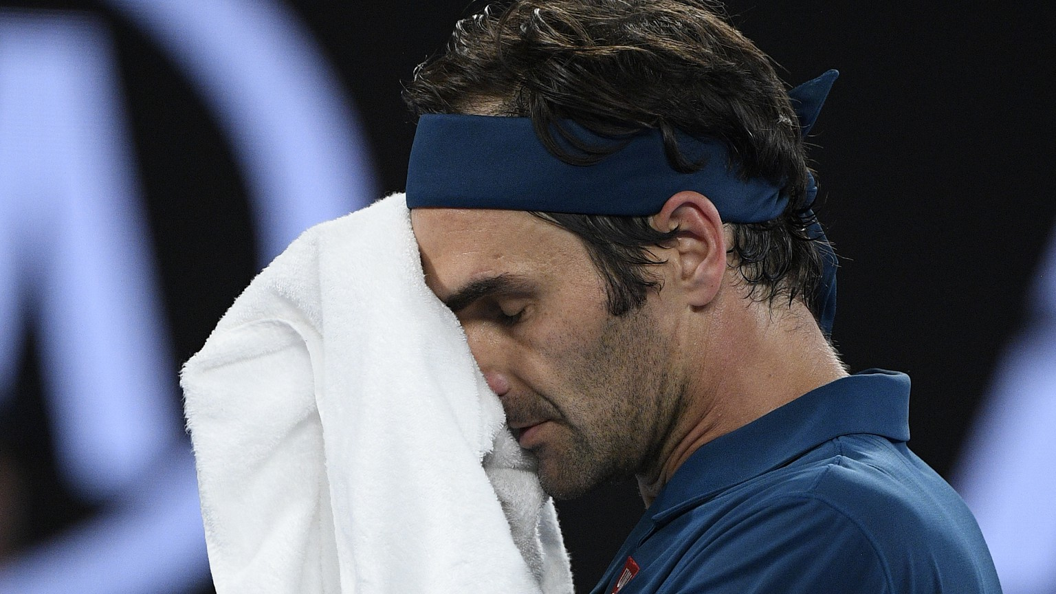 Switzerland's Roger Federer wipes the sweat from his face during his fourth round match against Greece's Stefanos Tsitsipas at the Australian Open tennis championships in Melbourne, Australia, Sunday, Jan. 20, 2019. (AP Photo/Andy Brownbill)