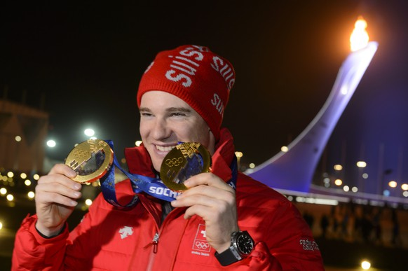 Cross country skiing 15km classic and skiathlon gold medalist Switzerland's Dario Cologna poses with his two gold medals in front of the Olympic Flame on the top of the Olympic cauldron after the victory ceremony of the men's cross country skiing 15km classic at the XXII Winter Olympics 2014 Sochi in Sochi, Russia, on Friday, February 14, 2014. (KEYSTONE/Laurent Gillieron)