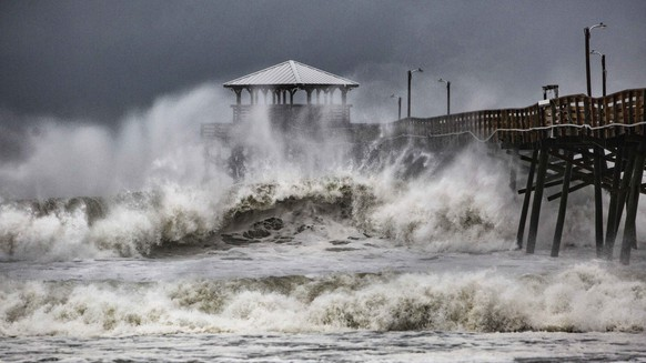 FILE - In this Sept. 13, 2018, file photo, waves slam the Oceana Pier & Pier House Restaurant in Atlantic Beach, N.C. as Hurricane Florence approaches the area.  U.S. Marine Corps leaders say it will cost around $3.6 billion to repair the extensive damage to Camp Lejeune in North Carolina from Hurricane Florence. (Travis Long/The News & Observer via AP, File)