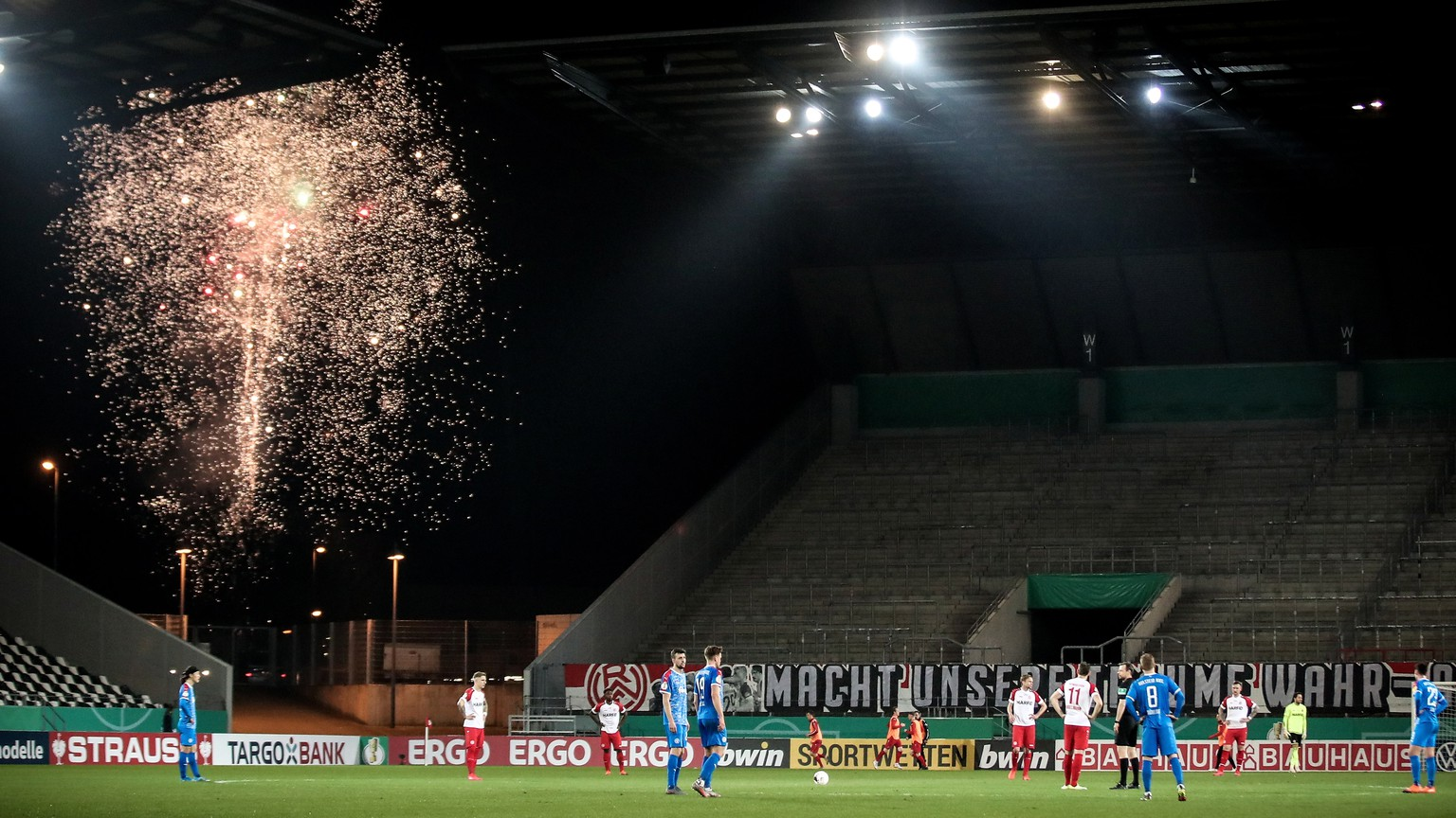 epa09049305 Fireworks illuminate the sky outside the stadium after Kiel scored the 1-0 lead during the German DFB Cup quarter final soccer match between Rot-Weiss Essen and Holstein Kiel in Essen, Germany, 03 March 2021.  EPA/FRIEDEMANN VOGEL / POOL DFB regulations prohibit any use of photographs as image sequences and/or quasi-video.