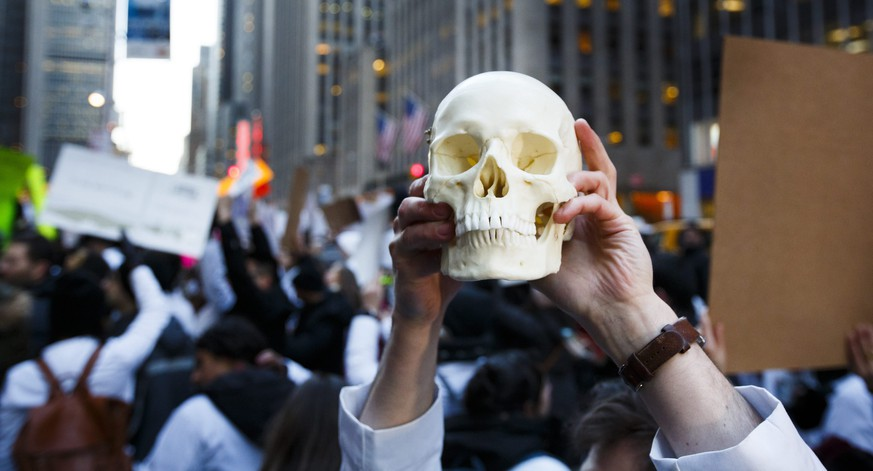 epa05762042 New York-area medical students, including one holding up a plastic human skull, gather to protest the proposed plan by the President Donald Trump and the Republican party leadership to repeal the Affordable Care Act (ACA), also known as Obamacare, in New York, New York, USA, 30 January 2017. Tomorrow is the deadline for people to sign up for the current version of the ACA and it unclear how the proposed repeal of the law will take shape.  EPA/JUSTIN LANE