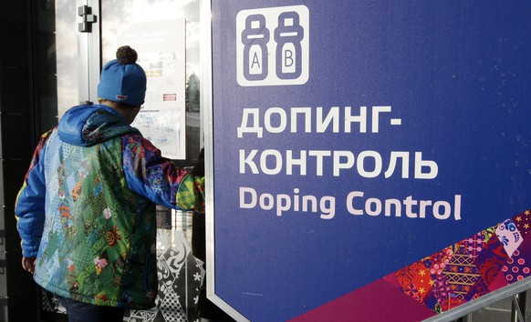 FILE - In this Feb. 21, 2014, file photo, a man walks past a sign reading doping control, at the Laura biathlon and cross-country ski center, at the 2014 Winter Olympics in Krasnaya Polyana, Russia. The IOC