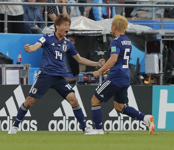 Japan's Takashi Inui, left, celebrates his side's opening goal with Japan's Yuto Nagatomo during the group H match between Japan and Senegal at the 2018 soccer World Cup at the Yekaterinburg Arena in Yekaterinburg , Russia, Sunday, June 24, 2018. (AP Photo/Vadim Ghirda)