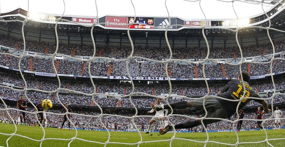 epa04463390 FC Barcelona's Chilean goalkeeper Claudio Bravo (R) couldn't stop the penalty kick scored by Portuguese Cristiano Ronaldo (L) of Real Madrid the ball during their Primera Division soccer match played at Santiago Bernabeu stadium in Madrid, Spain on 25 October 2014.  EPA/Juan Carlos Hidalgo