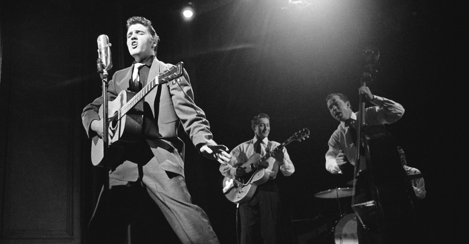This March 17, 1956 photo provided by courtesy of Taschen shows, Elvis Presley, left, and band members, Scotty Moore, on guitar, Bill Black on bass, and DJ Fontana on drums, during a live performance on
