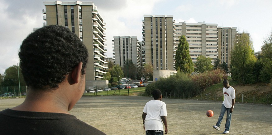 French boys play soccer in a waste ground by their low cost housing complex, Monday, Nov. 7,2005, in Grigny, a suburb south of Paris where, for the first time since the start of the urban violence, police has been targetted and injured by weapon's fire. France's tough low-cost housing projects were once desirable places to live for poor families, today, these housing projects at the heart of rioting across France.  (KEYSTONE/AP Photo/Jacques Brinon)