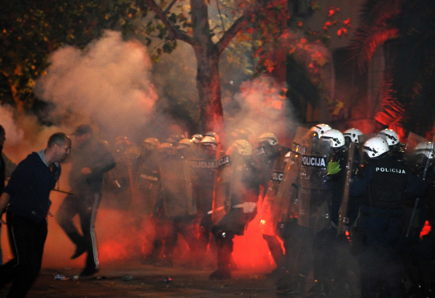 Montenegro police officers are engulfed in smoke and flames as opposition supporters hurled torches on them during a protest in front of the Parliament building in Podgorica, Montenegro Saturday, Oct. 24, 2015. Police fired tear gas at opposition supporters who hurled fire bombs and torches to demand the resignation Prime Minister Milo Djukanovic's government which hopes to steer the Balkan country toward NATO membership later this year. (AP Photo/Risto Bozovic)