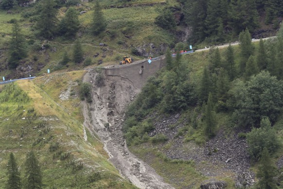 Worker use diggers to clean the road of the nineteenth stage of the Tour de France cycling race over 126,5 kilometers (78,60 miles) with start in Saint Jean De Maurienne and finish in Tignes, France, Friday, July 26, 2019. Organizers stopped the world's premier cycling event Friday for the riders' safety when a sudden, violent storm made the route through the Alps too dangerous. (AP Photo/Thibault Camus)