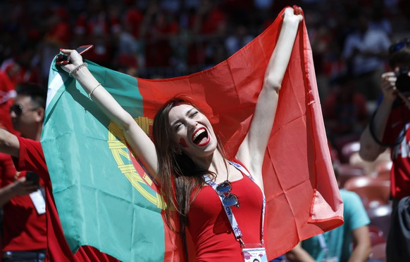 A woman holds a Portuguese flag prior to the group B match between Portugal and Morocco at the 2018 soccer World Cup in the Luzhniki Stadium in Moscow, Russia, Wednesday, June 20, 2018. (AP Photo/Hassan Ammar)