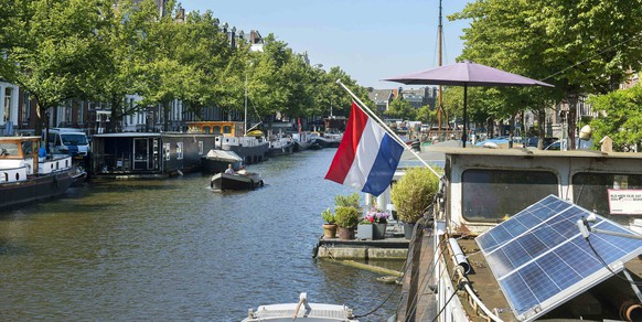 The national flag of the Netherlands is flown at half staff from a boat on the Keizersgracht canal during a national day of mourning for the victims of Thursday's Malaysia Airlines Flight MH17 plane disaster, in Amsterdam July 23, 2014. A Dutch air force transport plane carrying the first 16 coffins with the remains of victims of the downed Malaysian airliner took off on Wednesday from an airport in the eastern Ukrainian city of Kharkiv for the Netherlands. REUTERS/Toussaint Kluiters/United photos (NETHERLANDS - Tags: TRANSPORT DISASTER POLITICS CIVIL UNREST)
