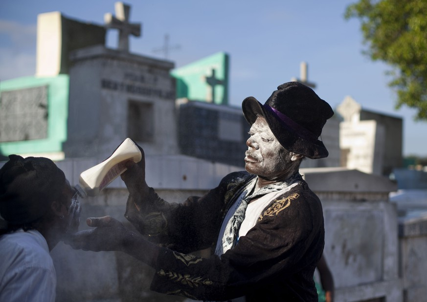 Charles Benest, a voodoo priest puts powder to the face of a believer during a Voodoo ritual that pays tribute to Baron Samdi and the Gede family of spirits during Day of the Dead celebrations at the National Cemetery in Port-au-Prince, Haiti, Sunday, Nov. 2, 2014. Day of the Dead traditions coincide with All Saints Day and All Souls Day on Nov. 1 and 2. (AP Photo/Dieu Nalio Chery)