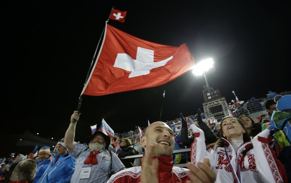 A fan waves a Swiss flag during the ski jumping large hill final at the 2014 Winter Olympics, Saturday, Feb. 15, 2014, in Krasnaya Polyana, Russia. (AP Photo/Gregorio Borgia)