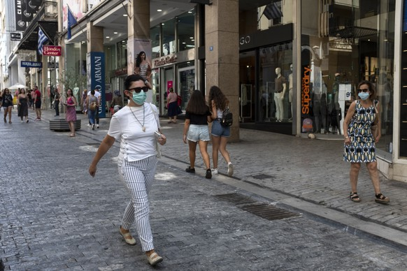 People make their way at a market street, in Athens, Thursday, Sep. 3, 2020. Greece has suffered a huge drop in output in the second quarter of the year, plummeting 15.2% on an annual basis, but the government insisted the figures did not worsen the country's annual outlook. (AP Photo/Yorgos Karahalis)