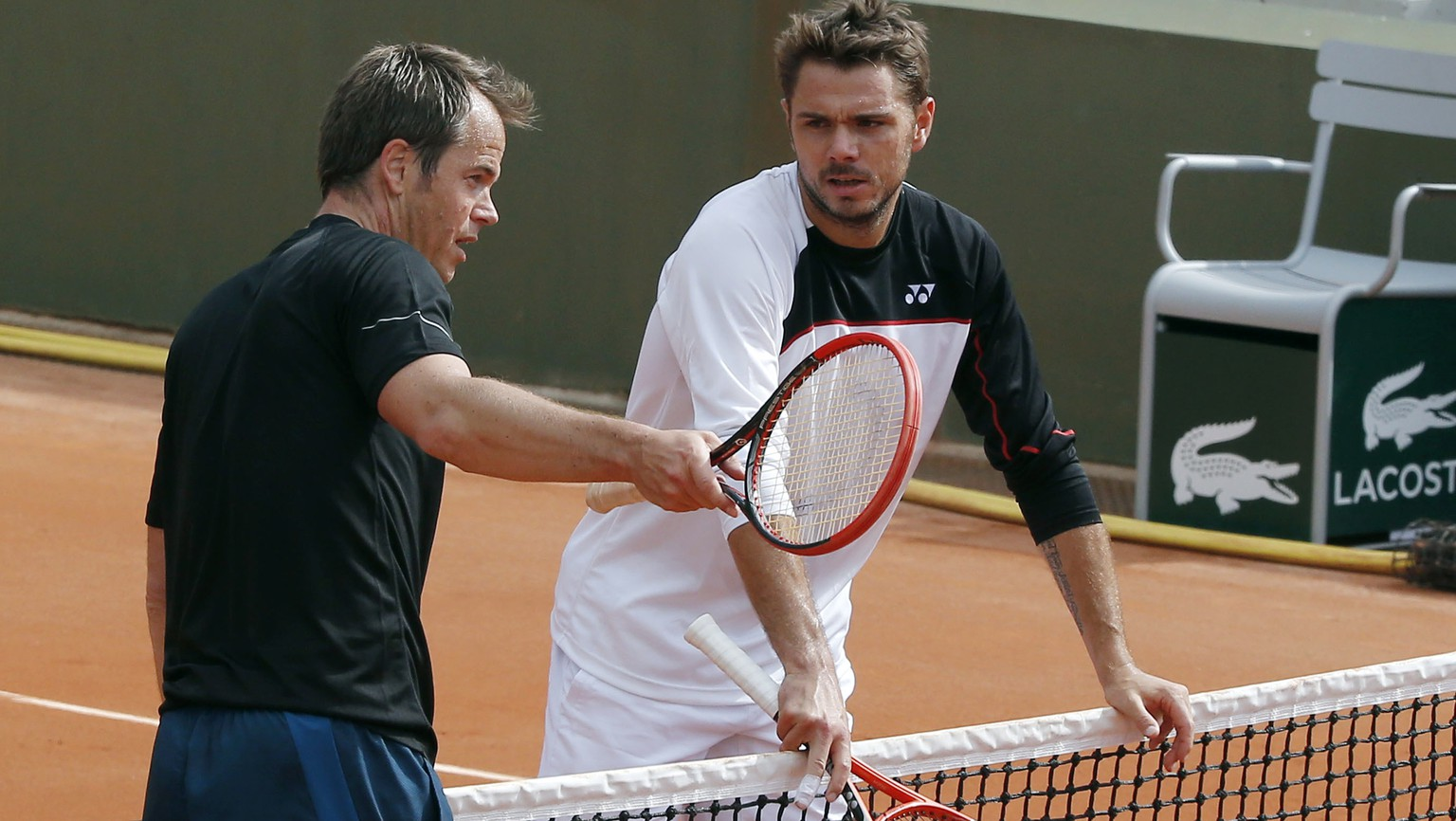 FILE - In this May 24, 2014, file photo, Stanislas Wawrinka, right, listening to his coach Magnus Norman during a training session for the French Open tennis tournament at Roland Garros in Paris.  Wawrinka needs a new coach, because Magnus Norman is moving on. Norman announced Wednesday, Oct. 25, 2017,  that he would be quitting the job after 4 and a half years as Wawrinka's coach, saying he wants to spend more time with his two young children. (AP Photo/Michel Euler, File)