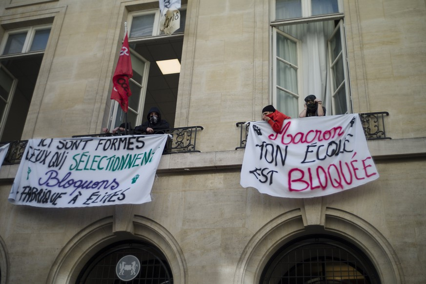 epa06676958 Students of the Sciences Po stand at the windows of the Political Institute during a blockage in Paris, France, 18 April 2018. Several universities across France have been occupied to protest against the government's labor and education reforms.  EPA/YOAN VALAT